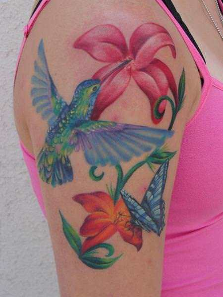 A Beautiful Tattoo Of A Hummingbird Sipping Nectar From A Bouquet Of Flowers