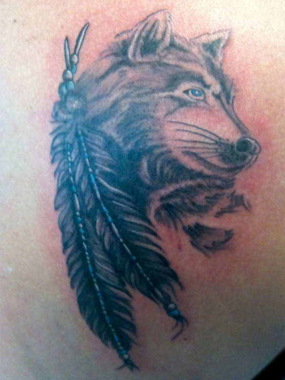Feathers And Wolf Tattoos On Lowerback