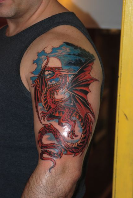 Fire Breathing Winged Dragon Tattoo On Muscles