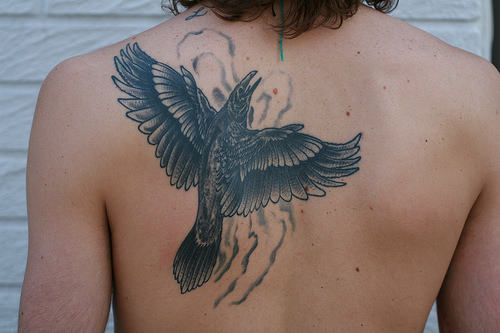 Flames And Flying Crow Tattoos On Back