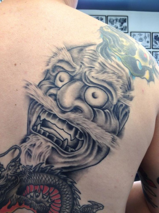 Grey Ink African Mask Tattoo On Back