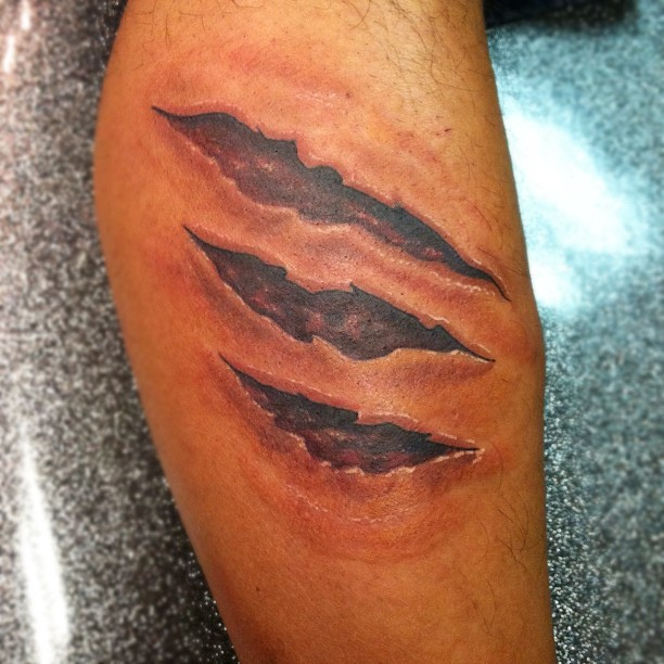 Grey Ink Arrow Ripped Skin Tattoo On Muscles