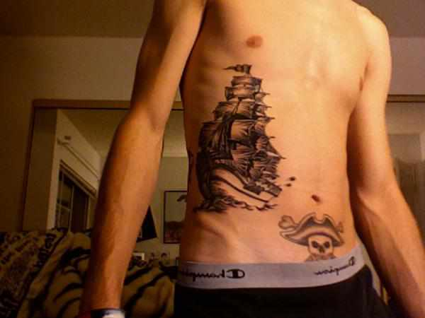 Grey Ink Ship And Pirate Skull Tattoos On Stomach