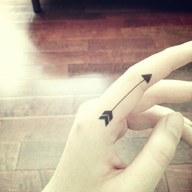 Little Size Black Arrow Tattoo On Side Of Finger