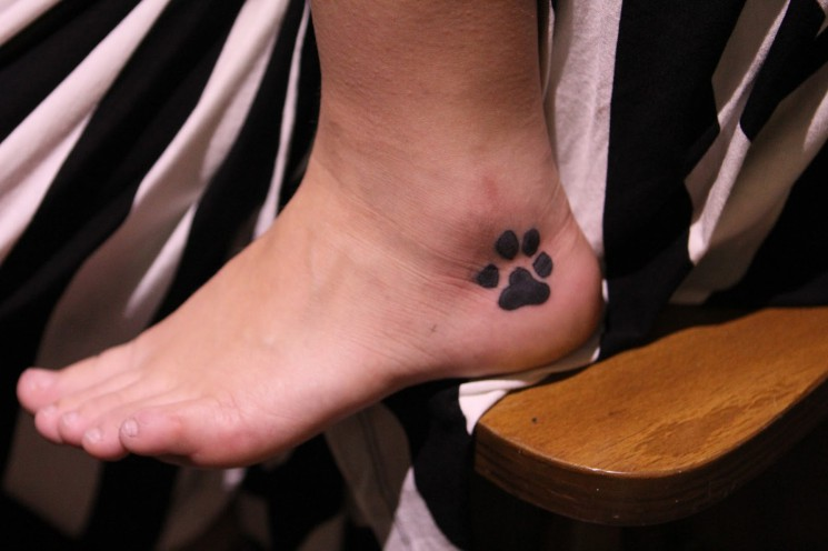 Name And Dark Black Paw Print Tattoos On Foot