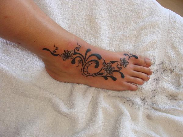 Owl Tattoo On Foot With Two Little Flowers