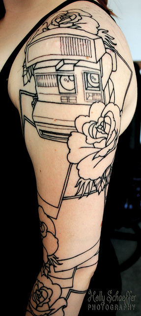 Polaroid Camera With Roses Tattoo On Sleeve