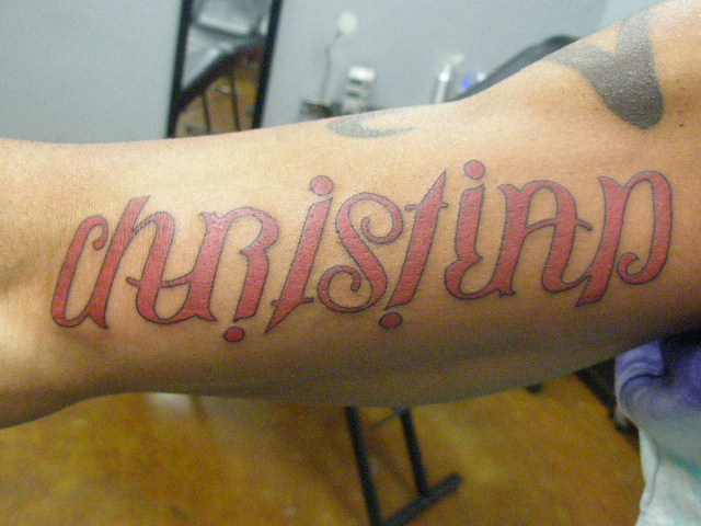 Red Ink Christian Word Tattoo On Arm