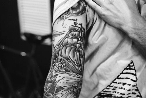 Showing Ship And Roses Tattoos On Arm