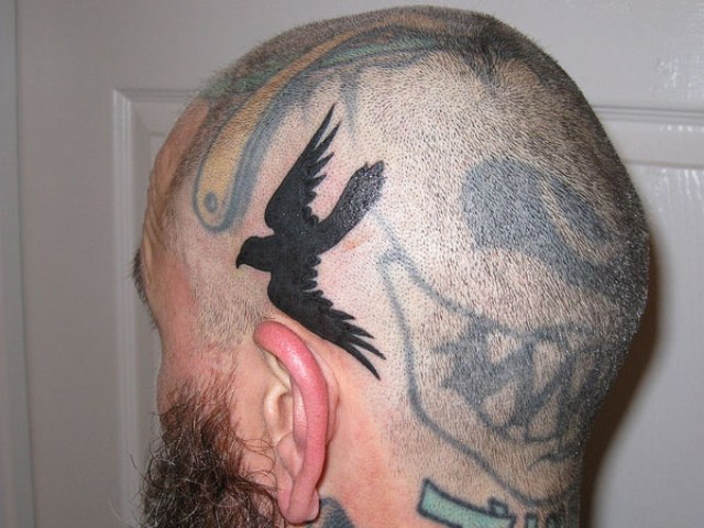 Small Flying Crow Tattoo On Head