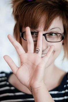 Smiling Girl With Small Skull Tattoo On Finger