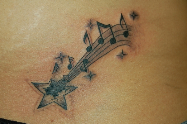 Star Turning Into Musical Notes Tattoo On Waist