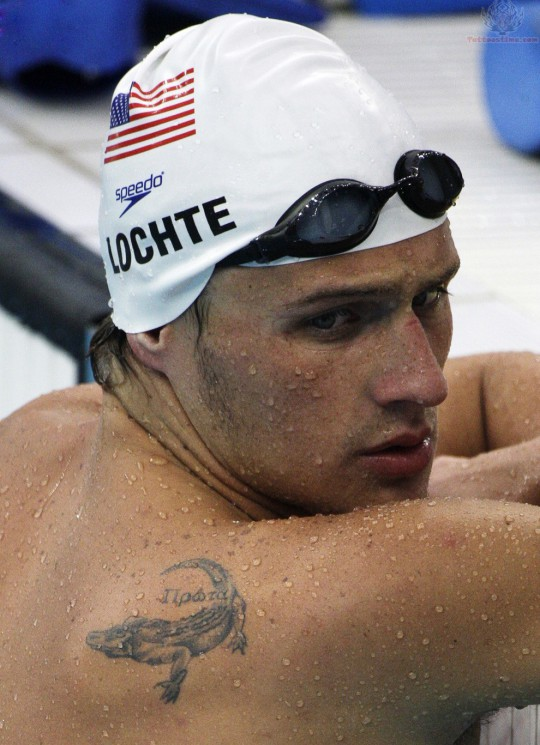 Swimmer With Olympic Rings Tattoo On Left Thigh