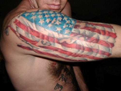 Torn Skin With Flag Tattoo On Upper Arm
