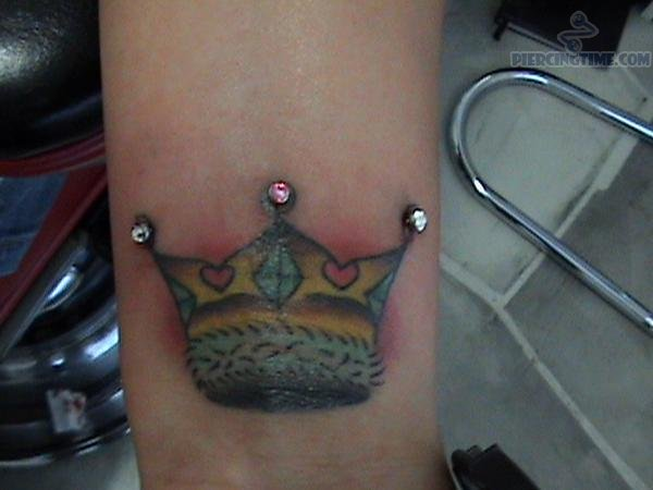 Triple Micro Dermals Wrist Piercing And Crown Tattoo