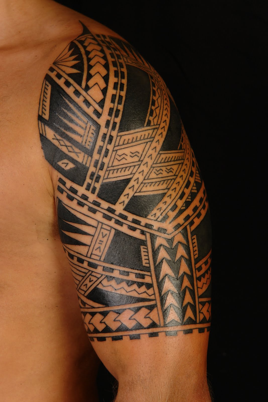 Black And Grey Ink Hawaiian Tribal Tattoo On Upper Back photo - 2
