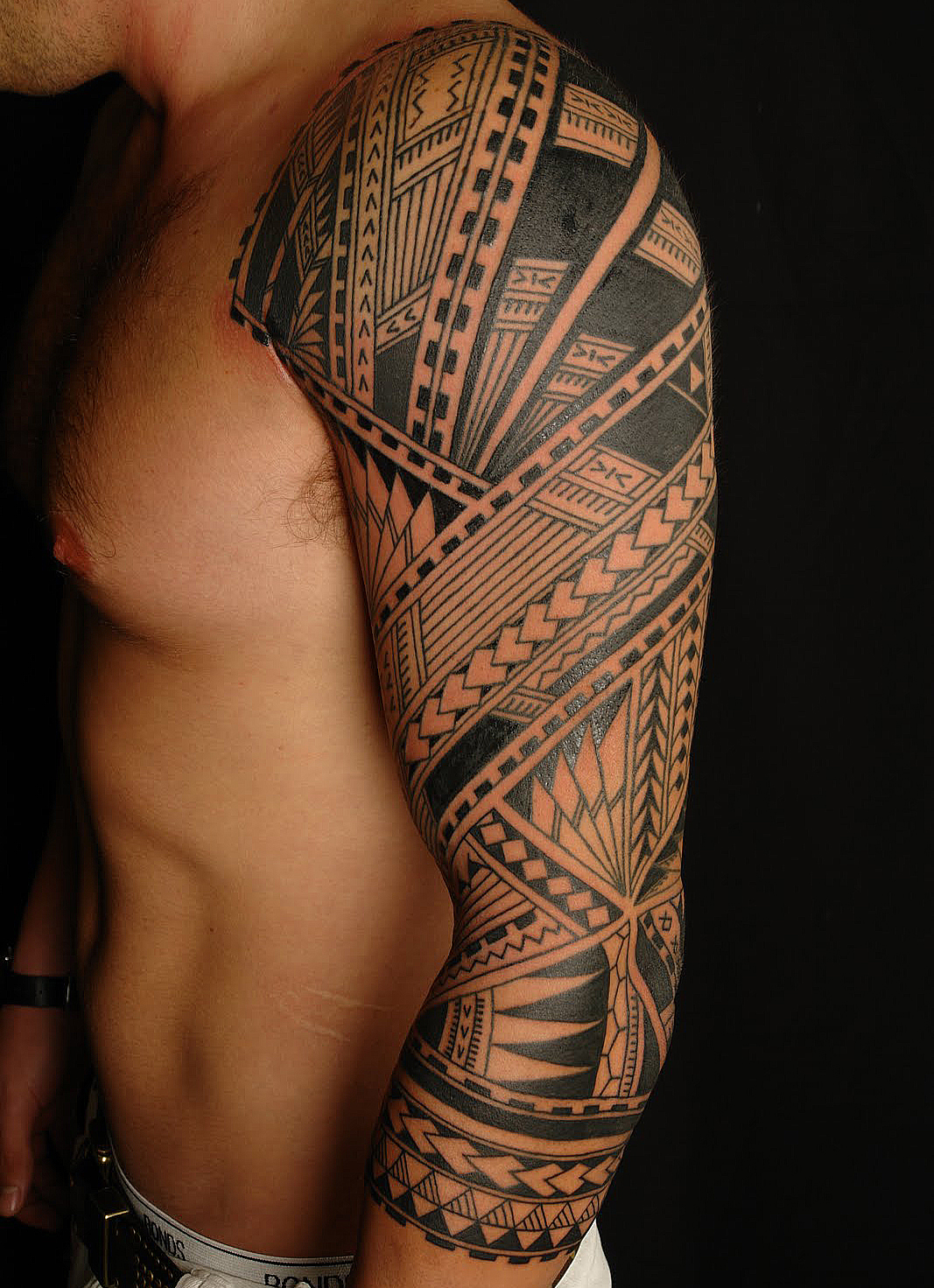 Black Ink Tribal Tattoos On Chest And Arm photo - 2