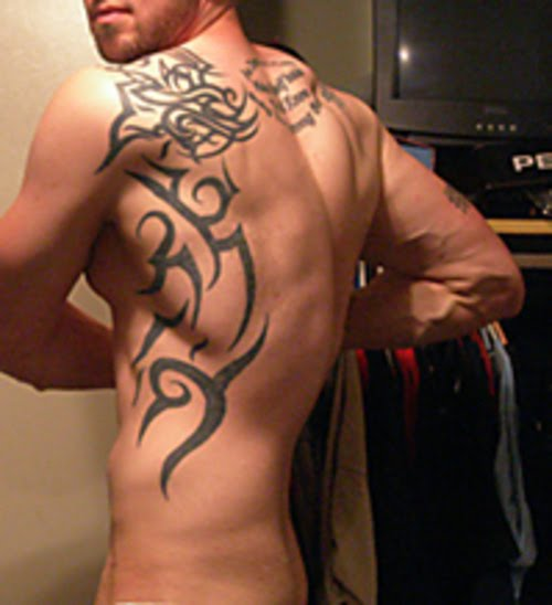Black Ink Tribal Tattoos On Chest And Arm photo - 3