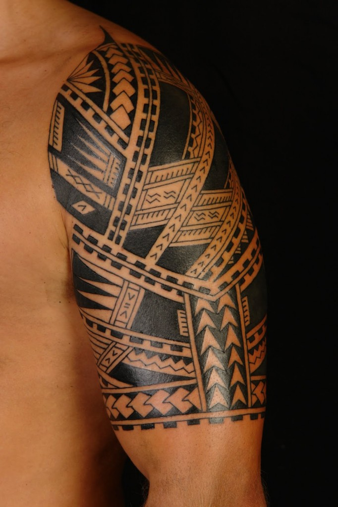 Black Ink Tribal Tattoos On Left Arm And Back photo - 2