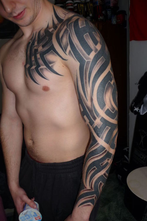 Glowing Black Ink Tribal Tattoo On Biceps photo - 1