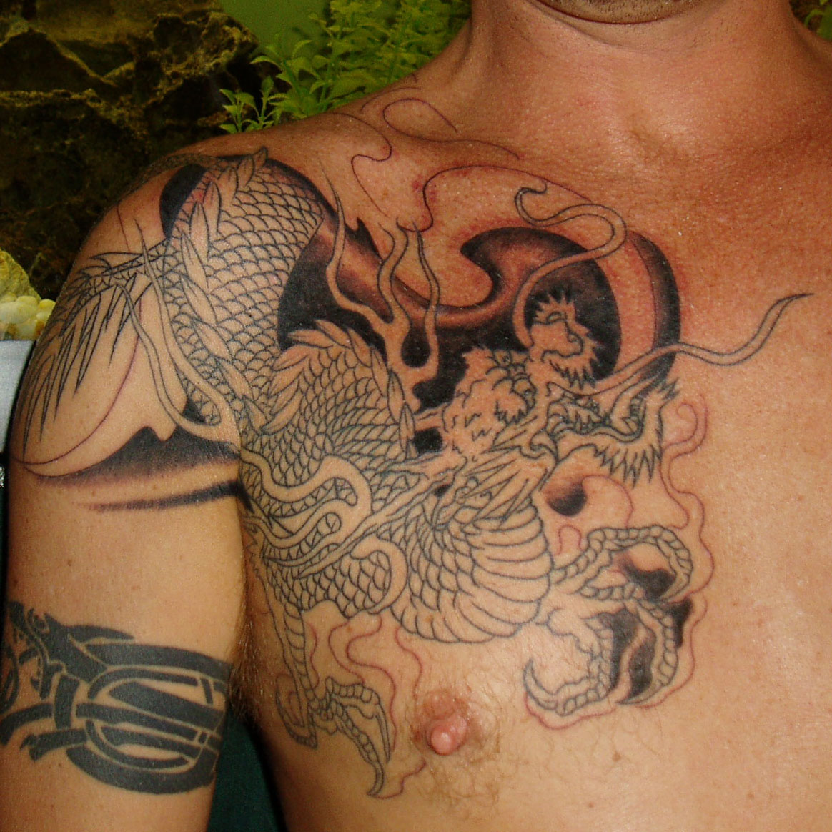 Grey Ink Japanese Mask Tattoo On Biceps photo - 1