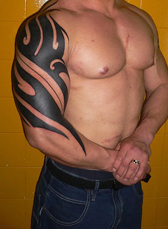 Grey Ink Tribal Tattoo On Back Of Body photo - 3