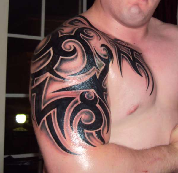 Nice Black Ink Tribal Tattoo On Chest And Arm photo - 1