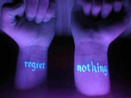 Regret Nothing Blacklight Tattoo On Wrist photo - 1